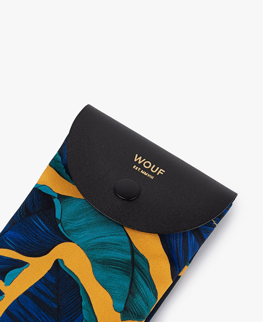 woman's mustard satin sunglass case with blue leaves and leather